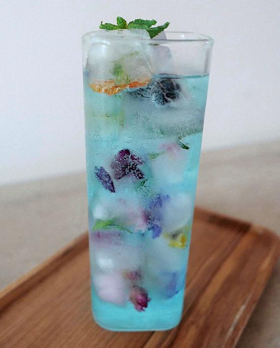 Ngoài nấu ăn đỉnh, Thanh Hằng còn có tài lẻ là pha chế cocktail cũng xịn xò không kém. Siêu mẫu có mẹo nhỏ là dùng trái cây và các loại hoa cho vào làm thành nước đá, sau đó dùng soda pha rượu, thêm chút chanh tạo cảm giác thơm thơm, cay nhẹ. Ly cocktail màu xanh mát như nước biển, sặc sỡ màu của trái cây và hoa, mang tới không khí ngày hè.