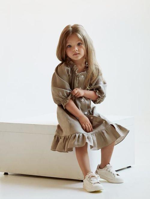 Váy hạ eo tông màu trung tính được trang trí thêm những đường bèo nhún điệu đà ở cổ áo, chân váy.