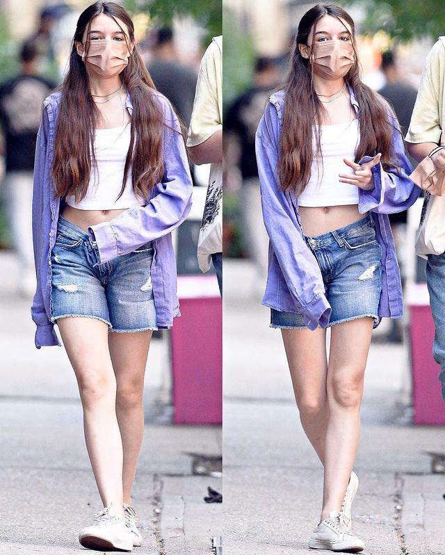 Suri thường ưa chuộng áo crop-top để lộ eo thon. Cô bé thoải mái dạo phố với giày thể thao, áo chống nắng denim.