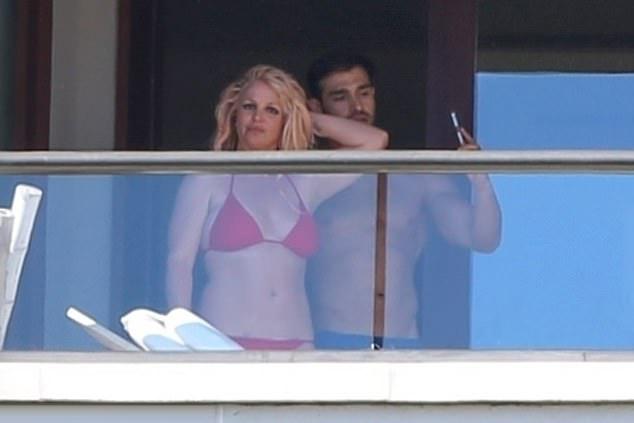 Britney và bồ trẻ được trông thấy chụp hình trên ban công khách sạn ở đảo Maiu. Britney mặc bikini đỏ nóng bỏng, để mặt mộc và thả mái tóc bồng bềnh tự nhiên.