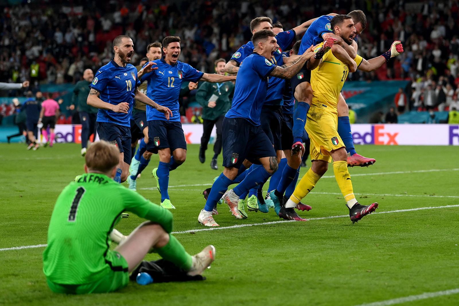 Các cầu thủ Italy đồng loạt chạy về phía Donnarumma sau khi anh cản được cú penalty cuối cùng, trong khi thủ môn Pickford phía Anh ngồi thừ trên sân.