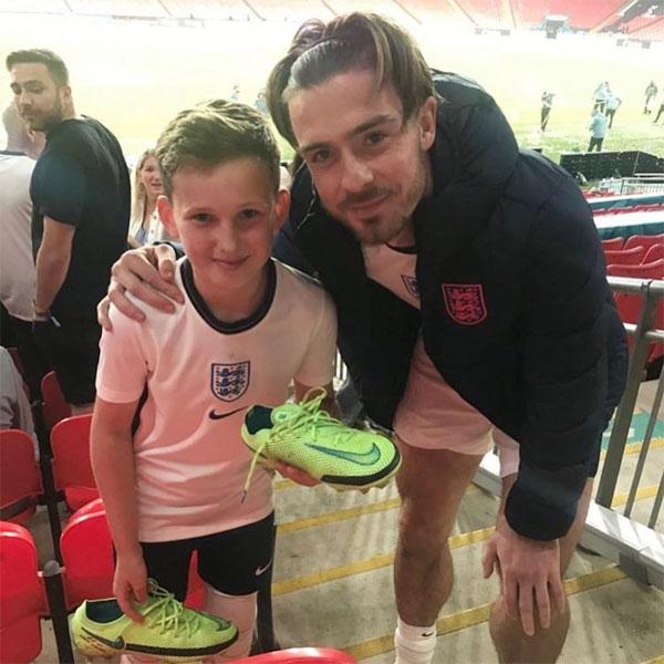 Tiền vệ Jack Grealish đưa đôi giày cho fan nhí rồi chụp ảnh với cậu bé. Ảnh: The Sun.