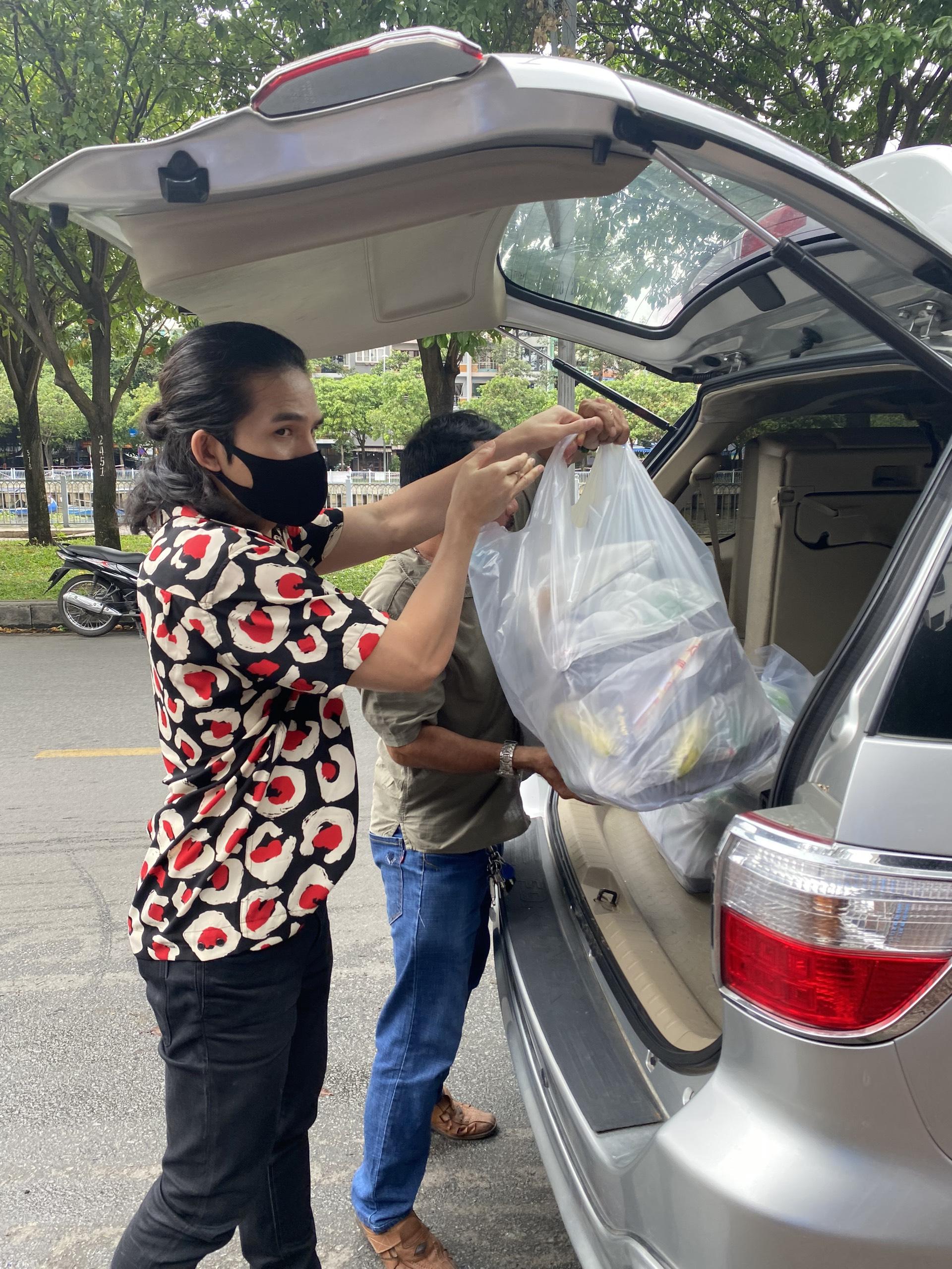 Ca sĩ Quốc Thiên phụ giúp vận chuyển cơm đến các điểm tập kết.