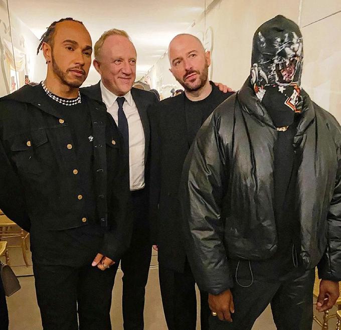 Kanye West tới Paris một mình dự show Balenciaga. Anh trùm mũ chụp ảnh với các khách mời.