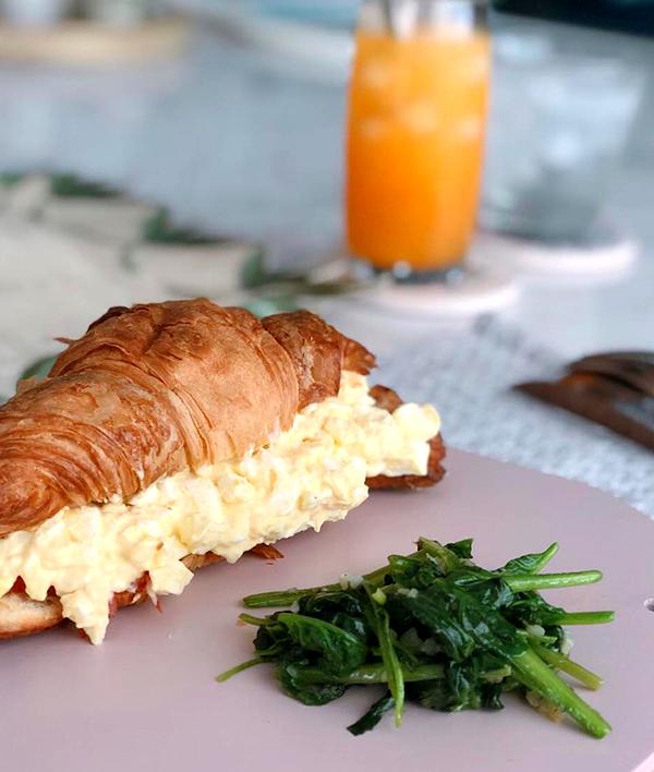 Khi không có thời gian, chị chồng Hà Tăng làm bữa sáng đơn giản hơn với bánh mì crossaint kẹp trứng, thịt hun khói, cà chua, ăn với rau cải xào tỏi. Sự kết hợp thú vị với một món ăn kiểu Âu và món rau kiểu Á nhưng khá đủ chất.