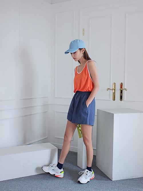 Set đồ cho bạn gái yêu sự năng động với cách phối áo ba lỗ tông cam nổi bật cùng quần short kiểu ống rộng.