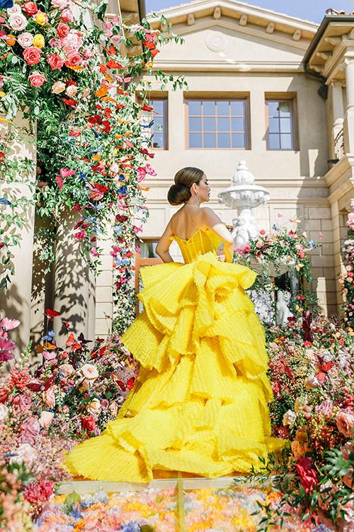 Mẫu đầm vàng được lấy ý tưởng từ những cánh bướm trong không trung và mang tới sự kiêu sa, quyền lực như nữ hoàng cho người diện. Mimi cho biết Đỗ Long đã cùng ekip xếp tỉ mỉ hàng trăm miếng vải, tạo độ phồng thành hình cánh bướm cho váy.