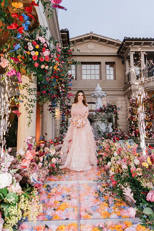 Tôi nghĩ người phụ nữ nào cũng ao ước được mặc một bộ váy hồng ngọt ngào, dịu dàng khi bước lên lễ đường. Vì thế, tôi đã chọn váy màu hồng làm váy thứ hai cho tiệc, chị nói. Mẫu đầm được đính kết tỉ mỉ bởi 4-5 nghệ nhân hàng nghìn viên đá Swarovski màu hồng với tổng chi phí vật liệu khoảng 5.000 USD.