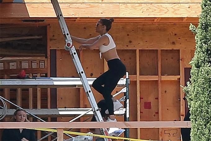 Ngôi sao nhạc pop mặc quần legging với áo crop-top gọn gàng, khỏe khoắn khi đi xem nhà.