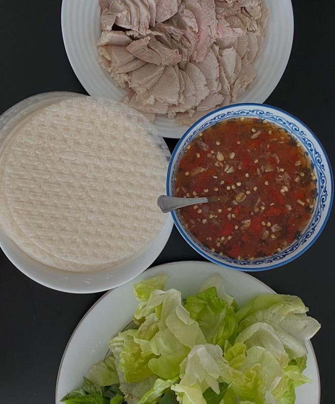Trong khi đó, cô chị Yến Trang lại thích món bánh tráng cuốn thịt heo. Hai chị em chấm với mắm ớt thay vì mắm nêm truyền thống. Đĩa rau tươi đầy ắp khiến nhiều người thèm thuồng giữa mùa dịch.