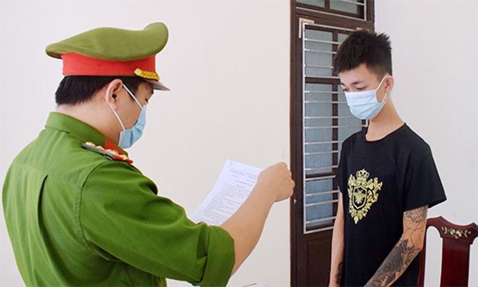 Nghi can Quốc (góc phải) nghe cảnh sát đọc lệnh bắt. Ảnh: H.Q