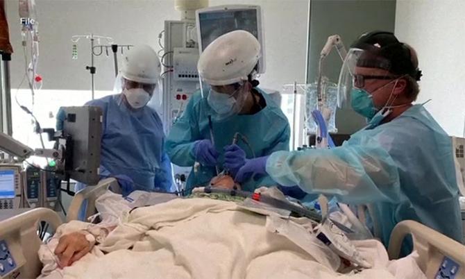 Các bác sĩ đang đặt nội khí quản cho một bệnh nhân Covid-19 nặng ở một bệnh viện tại Mỹ. Ảnh: AP.
