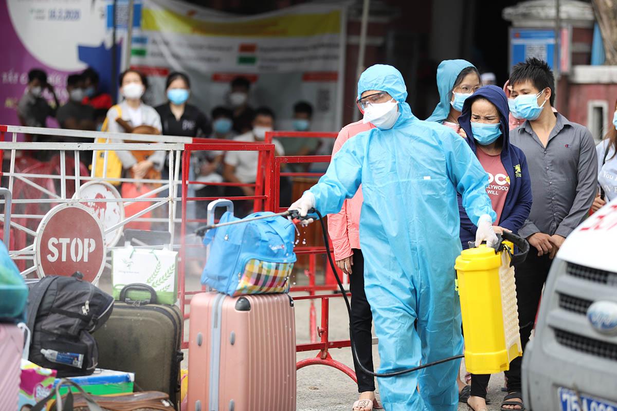Phun khuẩn hành lý người về từ TP HCM ở ga Huế. Ảnh: Vạn An