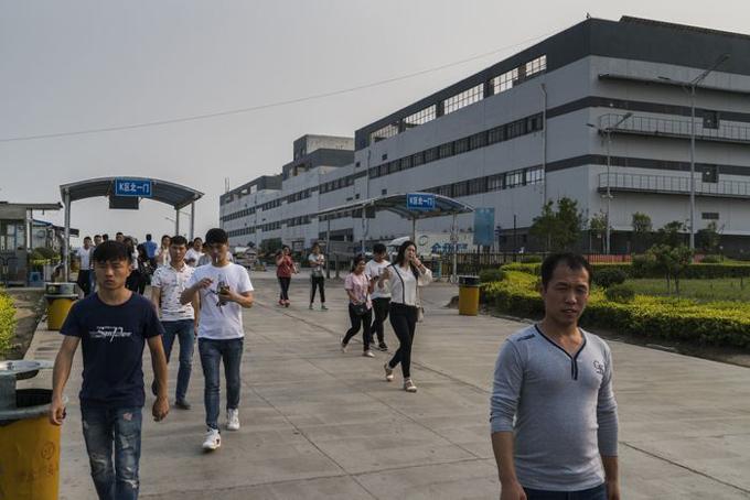 Công nhân Foxconn làm việc trong dây chuyền sản xuất iPhone tại một nhà máy ở Trịnh Châu, Trung Quốc, vào năm 2017. Ảnh: WSJ.