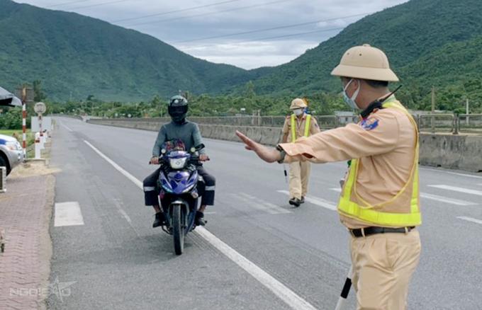 Một người dân đi xe máy từ các tỉnh phía Nam về quê được cảnh sát yêu cầu vào khai báo, chiều 27/3. Ảnh: Hùng Lê