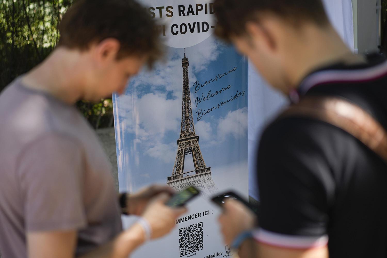 Du khách cài đặt ứng dung khi tham quan tháp Eiffel