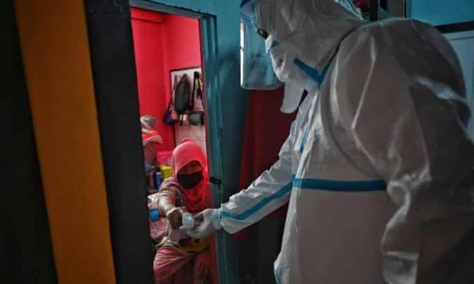 Một tình nguyện viên kiểm tra sức khỏe một phụ nữ mắc Covid-19 cách ly tại nhà ở quận Nong Chok, ngoại ô Bangkok vì giường bệnh cho bệnh nhân vẫn khan hiếm. Ảnh: AFP.