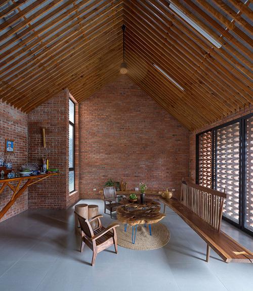 Phòng khách được thiết kế đơn giản với bộ bàn ghế gỗ cũ kỹ. Cả 3 phòng ngủ đều được lùi ra phía sau để đảm bảo sự riêng tư, tránh ồn ào khi nhà đông người.