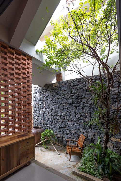 Hai bên nhà là tường rào xây bằng đá đen sẫm, được lấy trong quá trình đào móng cột công trình và san lấp sân. Tường đen xám, mộc mạc, gợi nhớ đến những bức tường đá của người dân tộc vùng núi nơi người chồng sinh sống.