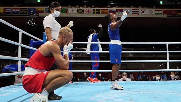 Ben Whittaker (áo đỏ) ngồi sụp xuống sàn đấu, ôm mặt thất vọng vì thua ở chung kết trước Arlen Lopez. Ảnh: Reuters.