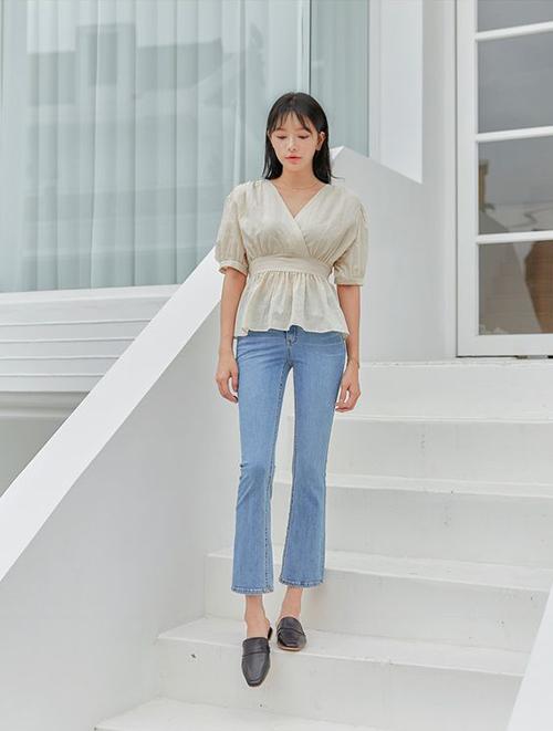 Sử dụng các mẫu áo trắng cách điệu đi cùng quần jeans xanh cũng là công thức phối màu được nhiều chị em công sở yêu thích.