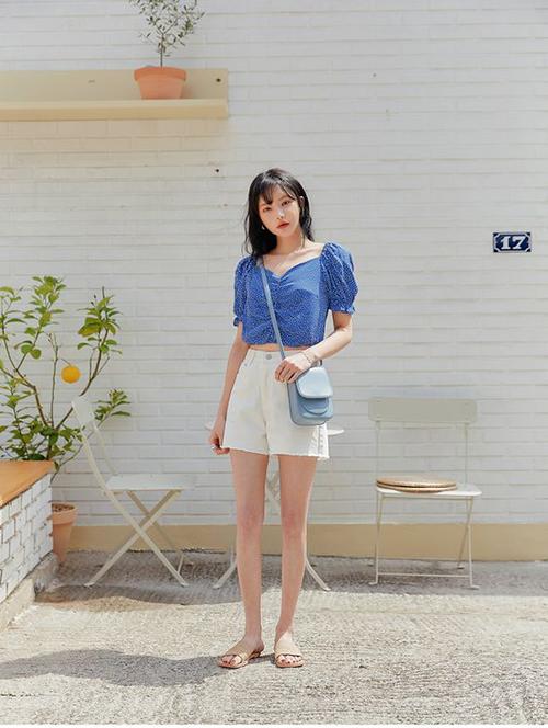 Áo tay bồng dáng lửng có tông xanh chủ đạo phù hợp với các bạn gái có làn da trắng sáng. Thiết kế này có thể phối cùng quần short, chân váy midi, quần âu ống đứng gam trắng.