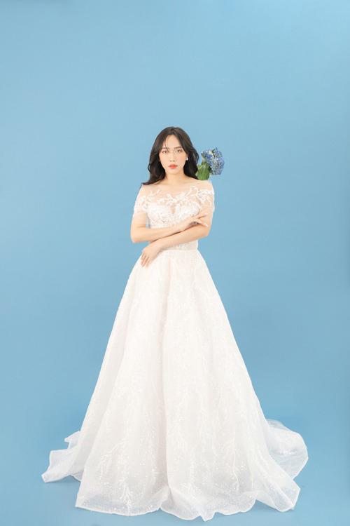 Bộ váy cưới trắng tinh khôi có phom dáng xòe, sử dụng cổ illusion với ren hoa, phần tay voan trễ xuyên thấu mang đến vẻ gợi cảm.