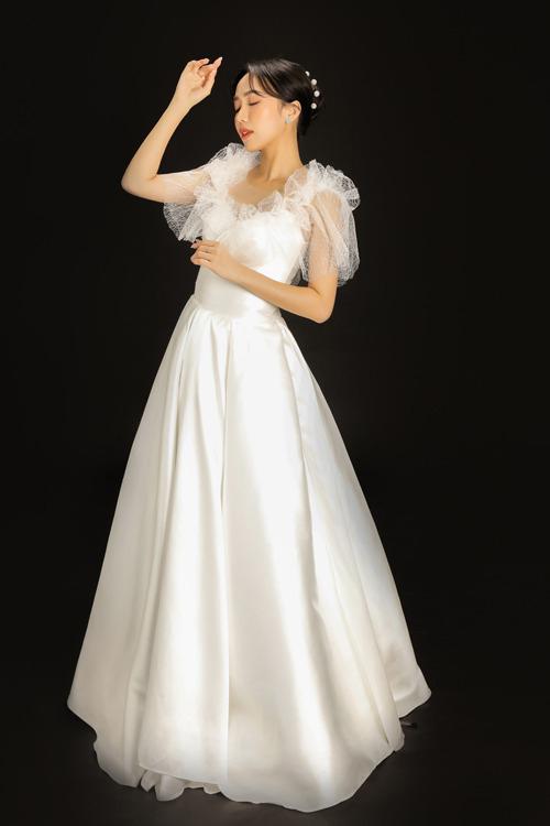 Đầm tối giản trở nên kiểu cách với tay nhún. Vải có độ bóng nhẹ giúp mang tới sự sang trọng, thanh lịch khi cô dâu diện.