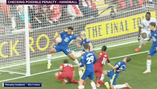 Phút bù giờ thứ nhất của hiệp một khi Chelsea đang dẫn 1-0, Liverpool tổ chức tấn công và tạo ra một pha bóng lộn xộn trước khung thành Mendy. Sadio Mane lao vào đá và bóng đập vào đùi rồi tay của hậu vệ Reece James bên phía Chelsea ngay sát vạch vôi trước khi ra ngoài. Trọng tài chính chờ bóng chết rồi xem lại tình huống bóng chạm tay James. Ảnh chụp màn hình