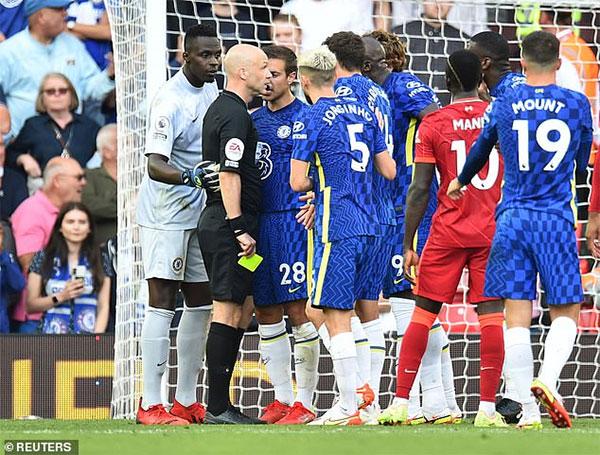 Sau khi xem xét, trọng tài rút thẻ đỏ hậu vệ Chelsea và cho Liverpool hưởng phạt đền. Các cầu thủ áo xanh phản ứng dữ đội khi đồng đội bị truất quyền thi đấu. Nhiều chuyên gia nhận xét trọng tài đã làm đúng theo luật mới vì Reece James đã không khép tay. Thủ thành Mendy của The Blues cũng bị thẻ vàng.. Ảnh: Reuters