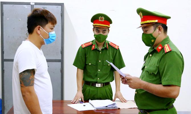Nghi can Điệp (áo trắng) nghe cảnh sát đọc lệnh bắt. Ảnh: Công an cung cấp