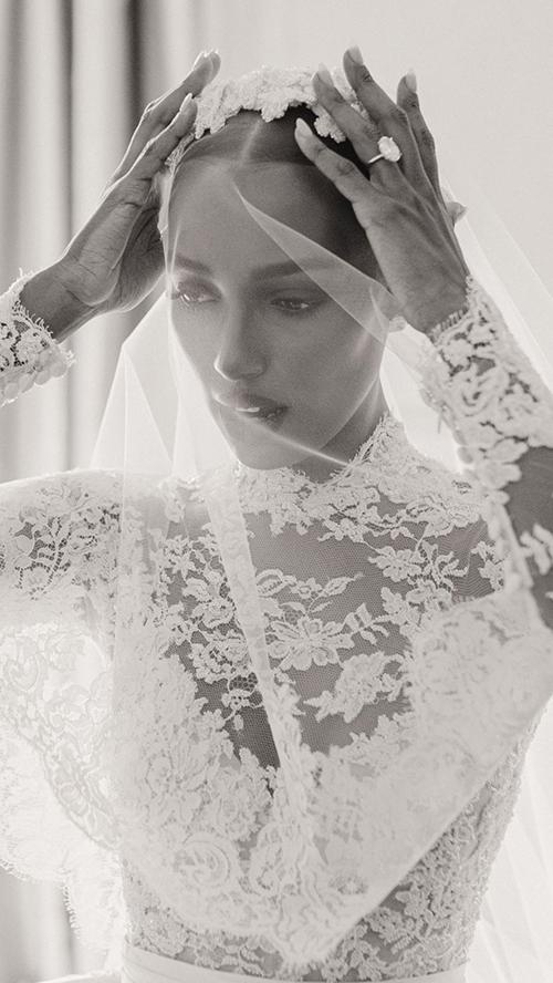 Vẻ ngoài của cô dâu khi diện váy. Đầm được làm từ vải lụa công nương, vải tuyn Italy, ren Pháp, có phần tà rời dài 4 m, phần trên có chi tiết ren tinh tế, ở dưới là vải có độ bóng, tối giản, được truyền cảm hứng từi đầm cưới kinh điển của cố Công nương Grace Kelly.