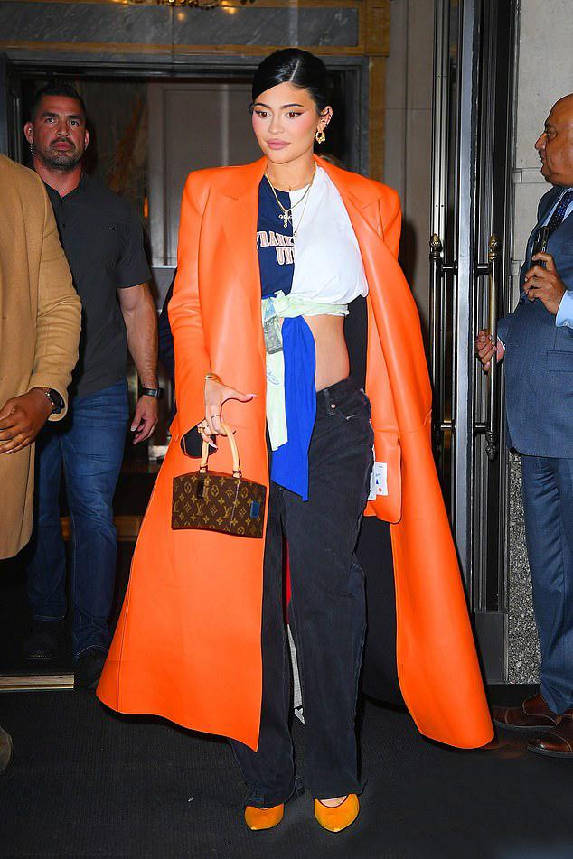 Kylie Jenner được đoàn vệ sĩ hộ tống rời khách sạn của cô. Người đẹp xuất hiện nổi bật trong chiếc áo khoác dài màu cam và đôi giày đồng điệu.