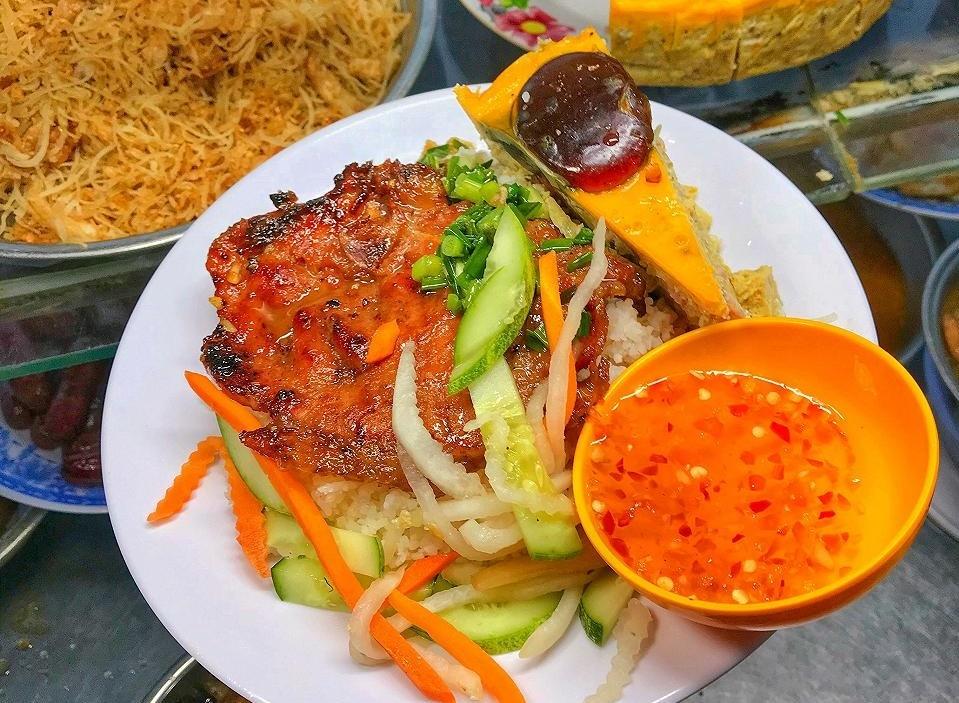 Còn nhắc đến ẩm thực Sài Gòn thì không thể bỏ qua đĩa cơm tấm trứ danh, món thích hợp để ăn cả buổi sáng, trưa, tối, khuya. Hạt gạo tấm rời rạc nhưng không bị khô, thấm một chút mỡ hành bóng mướt. Đặc biệt, miếng thịt cốt lết nướng tỏa hương thơm lừng chính là thứ gây thương nhớ nhiều nhất đối với các tín đồ ẩm thực. Thịt ướp trong nhiều giờ cho thật thấm vị, nướng trên bếp than tới khi rướm mỡ hấp dẫn, bày cùng một ít đồ chua, bì heo, chả trứng bắc thảo và chén nước mắm ngọt pha ớt là sết sẩy. Ảnh: Thi Thi
