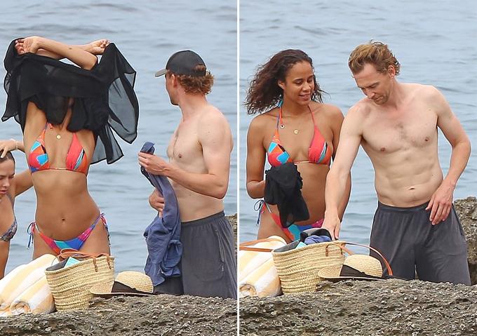 Zawe Ashton mặc bikini cam khoe dáng gợi cảm trong khi Tom Hiddleston cởi trần để lộ cơ bụng săn chắc.
