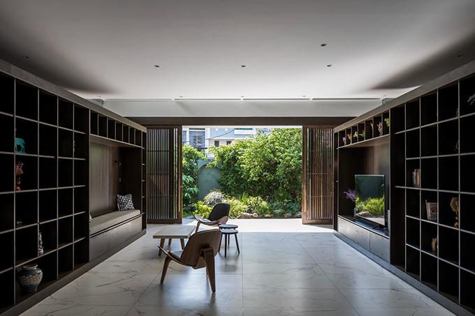 Từ phòng khách có thể nhìn ra vườn phía trước.  Nhóm KTS hướng đến việc tiết giảm trang trí, các không gian sử dụng vật liệu, ánh sáng tự nhiên cùng với cây xanh tạo nên những trải nghiệm thú vị.