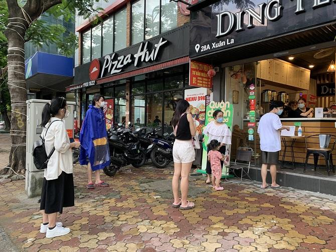 Nhiều người dân đứng xếp hàng mua trà sữa sau thời gian dài cửa hàng mở lại. Ảnh: Nguyễn Ngoan