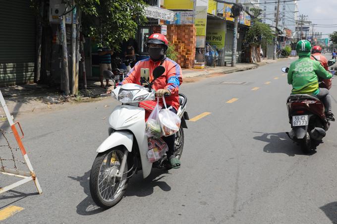 Tài xế một hãng công nghệ đi giao hàng tại quận 7, ngày 16/9. Ảnh: Quỳnh Trần.