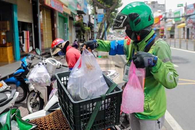 Một tài xế công nghệ nhận đơn hàng từ một quán giải khát ở quận 7, ngày 16/9. Ảnh: Quỳnh Trần.