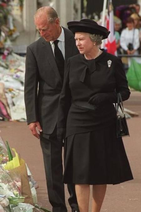 Nữ hoàng và Hoàng thân Philip bước đi bên hàng triệu bó hoa mà người dân đặt trước cổng Điện Kensington để tưởng nhớ Diana. Ảnh: Rex