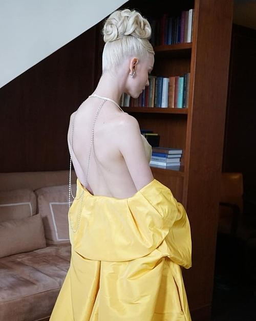 Ngôi sao của The Queens Gambi khoe trọn lưng trần và vóc dáng mảnh dẻ trong bộ váy dạ hội Dior Haute Couture. Thiết kế hai dây màu nude với đường cắt sắc nét giúp nữ diễn viên khoe khoảng hở táo bạo. Bộ cánh lấy cảm hứng từ phong cách cổ điển còn được trang trí vòng kim cương có giá khoảng 800.000 USD.