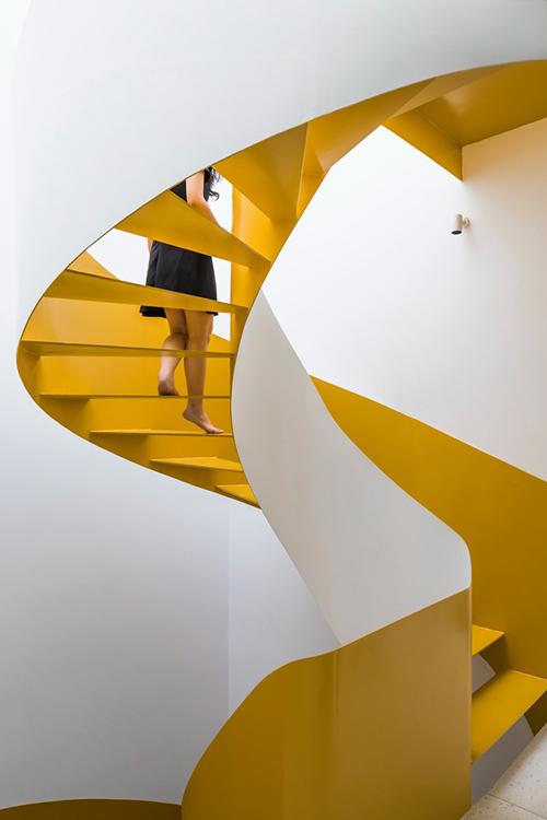 Cầu thang xoắn màu vàng là một điểm nhấn phá cách cho nhà màu trắng.