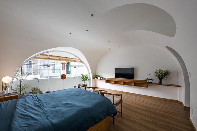 Tường được tạo hình theo đường cong, giúp phòng ngủ có đường nét mềm mại.