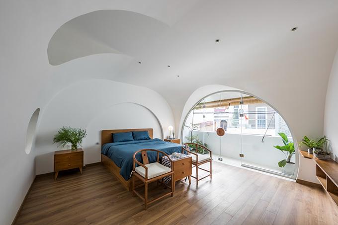 Phòng ngủ rộng lớn đón nắng qua cửa kính vòm.
