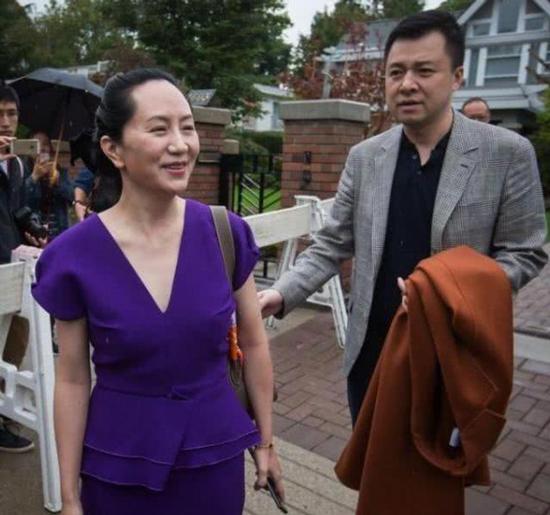 Chồng Meng Wanzhou cầm áo khoác giúp vợ khi bà trả lời phóng viên bên ngoài nhà riêng ở Vancouver năm ngoái. Ảnh: Sohu.