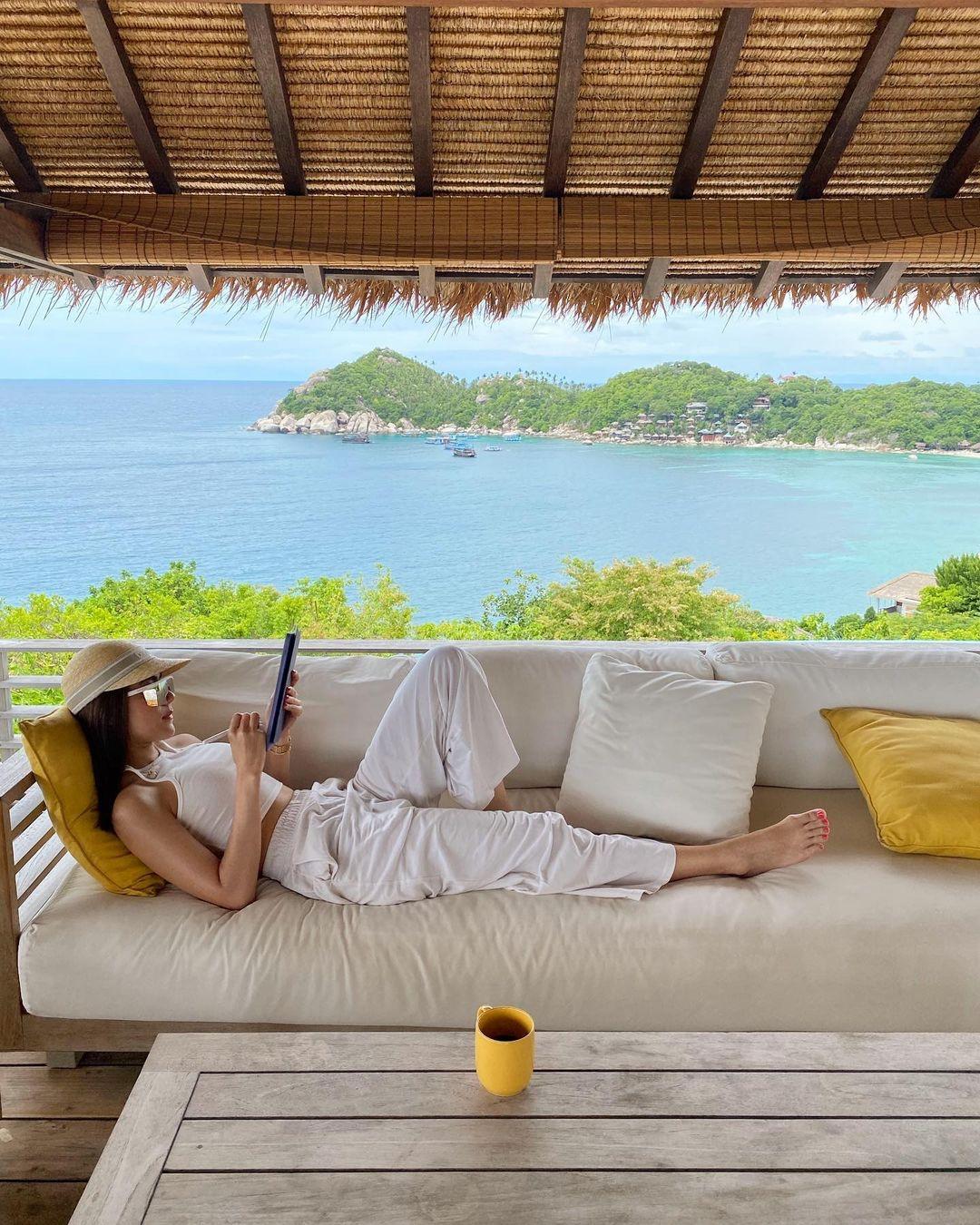Kimberley thảnh thơi nằm trên salon ngoài ban công phòng ngủ đọc kịch bản. Phong cách thiết kế của resort pha trộn giữa nét hiện đại và truyền thống Thái Lan, tạo cảm giác thoải mái. Các chòi nghỉ lợp mái tranh mộc mạc trong khi các biệt thự