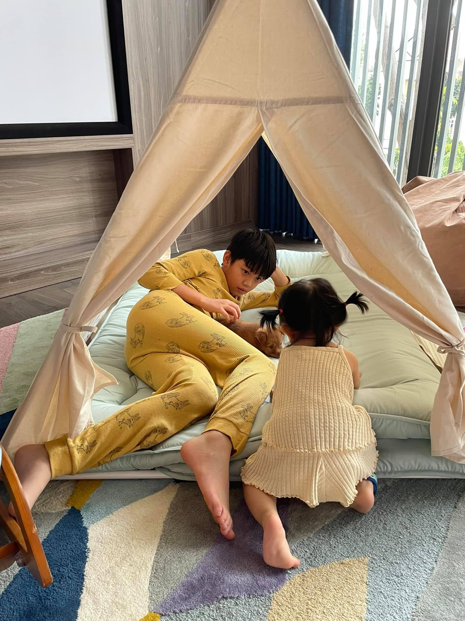 Cuối tuần trước, vợ chồng Cường Đôla bắt tay vào dựng một khu lều trại nhỏ tại gia cho hai con vui chơi những ngày nghỉ. Home camping (cắm trại tại nhà) đang là xu hướng của người Sài Gòn hai năm gần đây bởi vừa an toàn, lại xả stress mà không phải đi xa. Nhà có sân vườn rộng thường dựng lều trại ngoài trời, kết hợp tổ chức tiệc BBQ cùng gia đình. Còn nhà chung cư có thể tận dụng ban công, chọn chiếc lều nhỏ để chill.