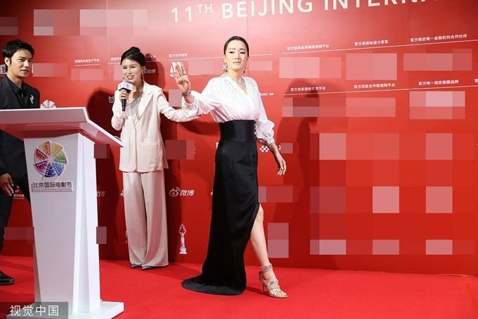 Củng Lợi sải bước tự tin, thể hiện đẳng cấp minh tinh quốc tế trên thảm đỏ sự kiện. 10 ngày đồng hành cùng LHP quốc tế Bắc Kinh, cô được báo chí dành nhiều lời khen ngợi cho các set đồ trang nhã và chủ yếu sử dụng hai tone màu đen - trắng.