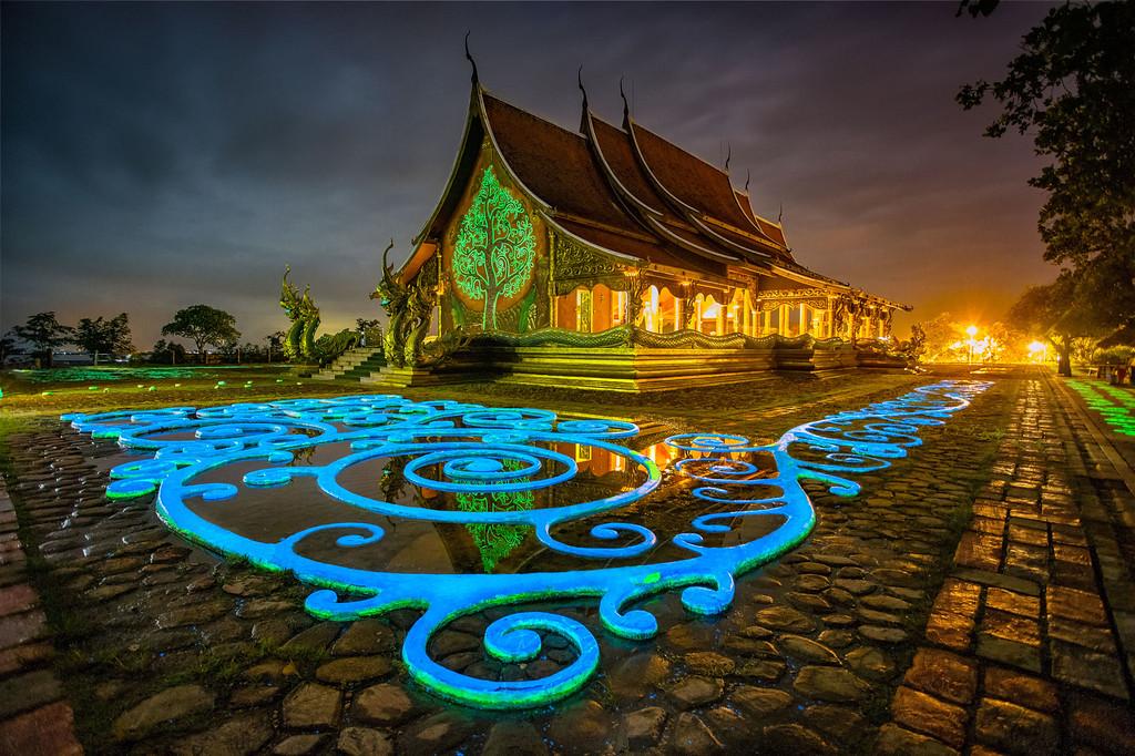 Wat Sirindhorn Wararam nằm gần biên giới Lào trông không mấy khác biệt so với nhiều ngôi đền khác ở vùng này. Tuy nhiên, khi mặt trời lặn, cũng là thời điểm tham quan lý tưởng, đền khoác lên diện mạo mới. Màn đêm buông xuống, lớp sơn huỳnh quang bên ngoài phát sáng tạo thành một cái cây sự sống nổi bật trong bóng tối. Ảnh: Fanclubthailand