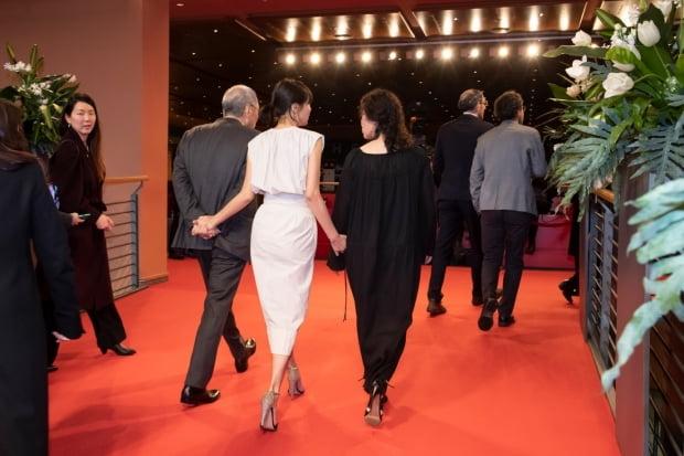 Cặp đôi nắm tay nhau từ phía sau, khi dự Liên hoan phim Berlin lần thứ 70.